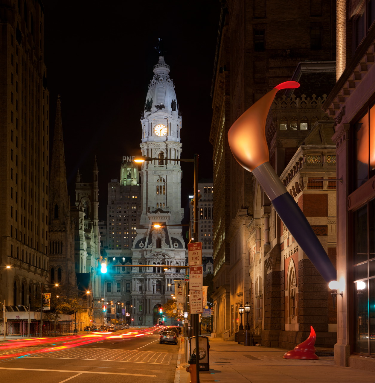 pop sculpture of 53 foot high paint torch by Claes Oldenburg lit with LED lights inside head of paintbrush and inside glob of paint with city hall in background