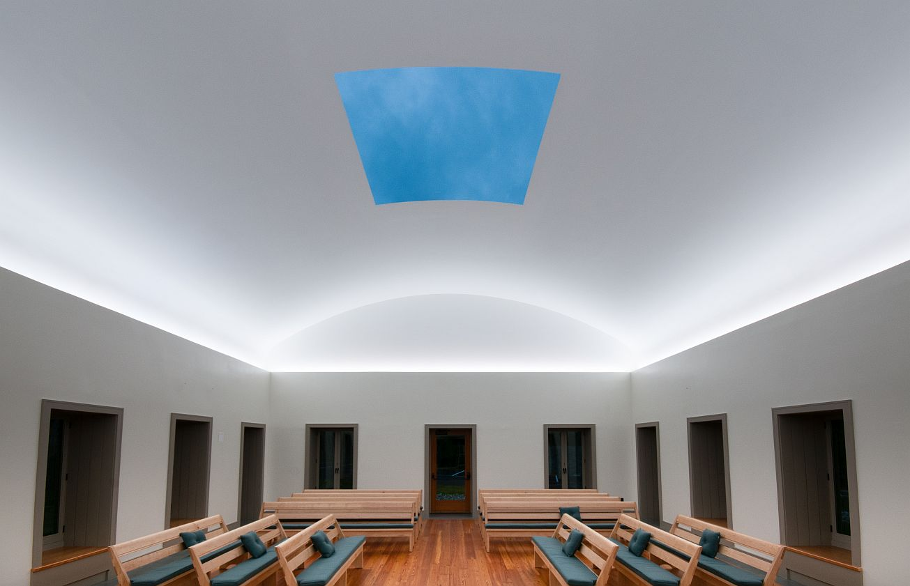 Skyspace interior view of James Turrell's retractable roof inside quaker meeting house at sunset. The windows are dark but the open roof is blue and lit up, as are the walls lit with light that make the arced ceiling appear to be glowing.