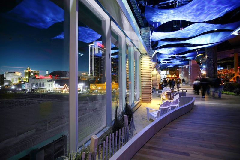 Adirondack chairs and sand facing bay floor-to-ceiling windows -inside of the renovated pier. The commercial fit-out project included special details and seaside touches, like this seating area facing the boardwalk ocean for guests to watch the sunset.